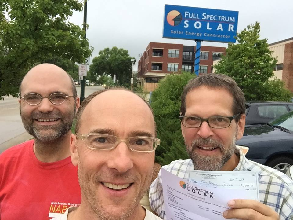 Brian Lavendel and friends smiling in front of blue Full Spectrum Solar sign