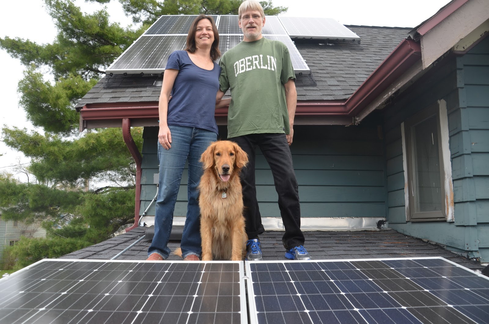 Toland and Passos standing on roof with solar panels and golden retriever
